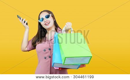 Happy Asian Woman Casual Clothes Holding Credit Card And Shopping Bags On Light Yellow Background.