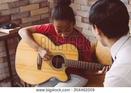 African American Girl In Casual Outfit Learning How To Play Guitar While Sitting On Couch Near Male