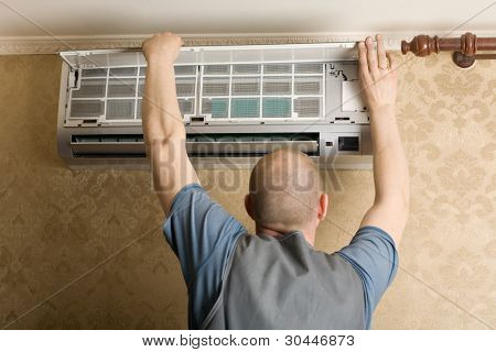 Adjuster air conditioning system sets a new air conditioner in the apartment.