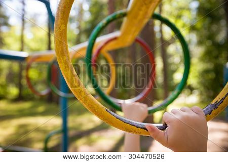 Young Boy Climbing On The Playground During The Summer. The Child Likes To Climb The Monkey Bar On T