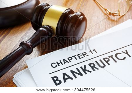 Stack Of Papers About Chapter 11 Bankruptcy And Glasses.