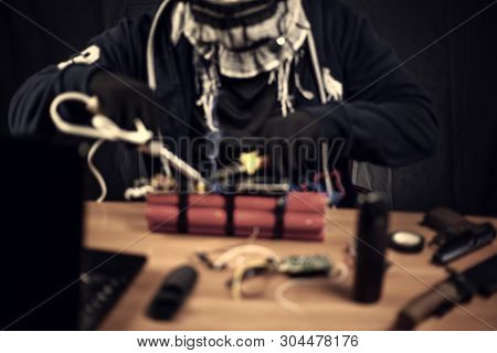 Terrorist In Gloves Makes A Bomb In The Room, On The Table Are A Gun, A Knife And A Phone, Blurry, T