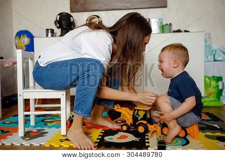 Side View Of Young Mother Sitting On Child Chair And Soothing Crying Baby While Playing With Cars In