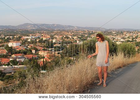 Tall Teenage Girl In A Short Gray Summer Dress And Sunglasses Standing On A Mountain Road With A Pan