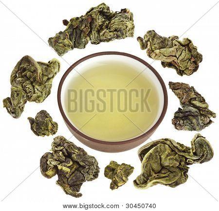 Bolas de té verde oolong en vaso de agua de arcilla aislado en blanco