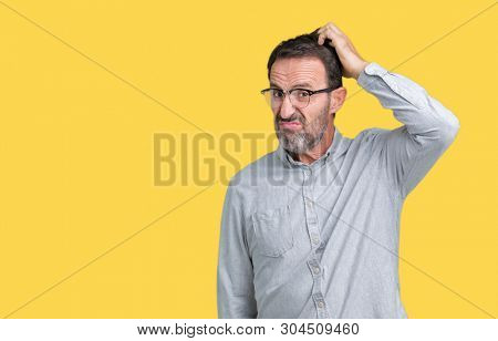 Handsome middle age elegant senior man wearing glasses over isolated background confuse and wonder about question. Uncertain with doubt, thinking with hand on head. Pensive concept.