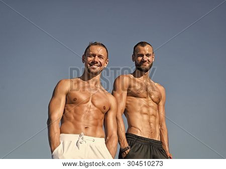 Men muscular body posing confidently with hands in pockets. Sport and bodycare. Muscular masculine guys look confident. Men sexy muscular bare torso stand outdoor. Sportsmen muscular belly posing. poster