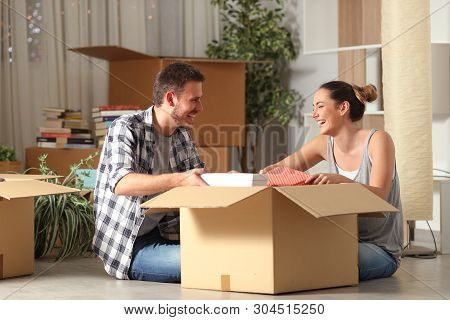 Happy Couple Laughing Unboxing Belongings Moving House Sitting On The Floor In The Night