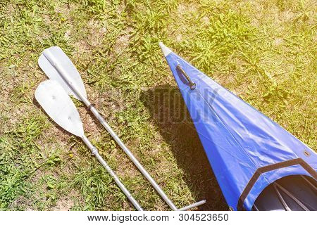 Whitewater Kayak With A Paddles On Green Grass Shore