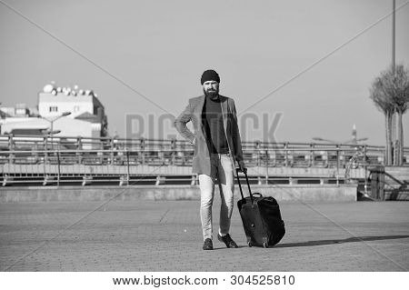 poster of Moving to new city alone. Hipster ready enjoy travel. Carry travel bag. Man bearded hipster travel with luggage bag on wheels. Traveler with suitcase arrive airport railway station urban background.
