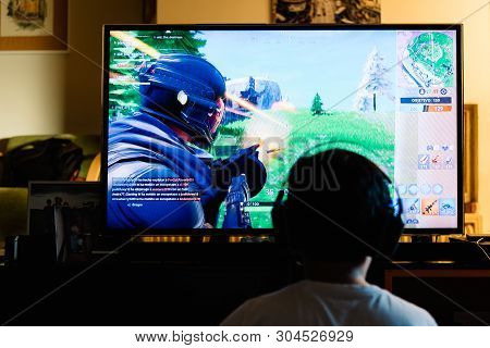 Teenager Playing Fortnite Video Game With Playstation On Tv