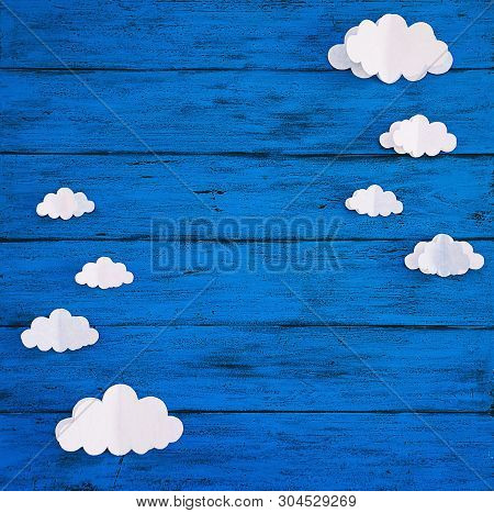 Paper Handmade Crafts Clouds On The Blue Wood Background. Top View, Copy Space.