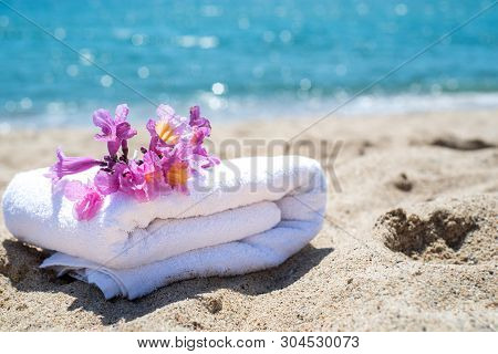 White Towels And Flowers With Ocean Scene. Stacked White Spa Towels On The Blue Indian Ocean Backgro