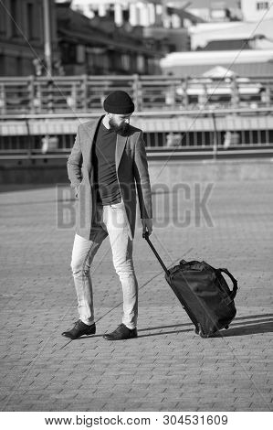 poster of Adjust living in new city. Traveler with suitcase arrive airport railway station urban background. Hipster ready enjoy travel. Carry travel bag. Man bearded hipster travel with luggage bag on wheels.