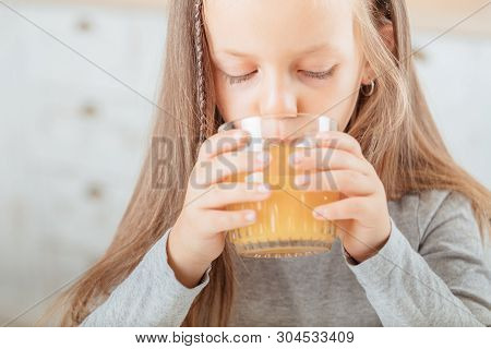 Natural Fruit Nutrition. Closeup Of Cute Little Girl Drinking Orange Fruit Juice In Kitchen. Blur Ba