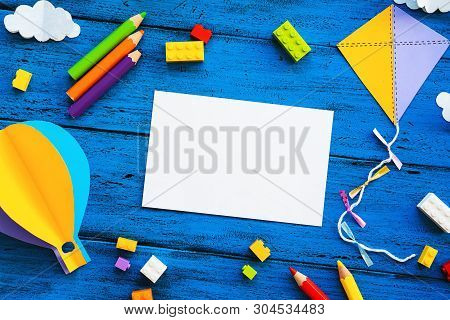 Сolourful Toy Bricks, Paper Crafts And Blank Card On Blue Wood Board. School Or Preschool Creative B