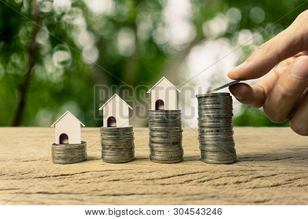 Home Loan, Mortgage, Property Investment, Asset Refinance Concept. A Man Hand Holding Coin And A Sma