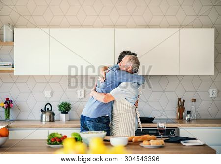 An Adult Hipster Son And Senior Father Indoors At Home, Hugging When Cooking.