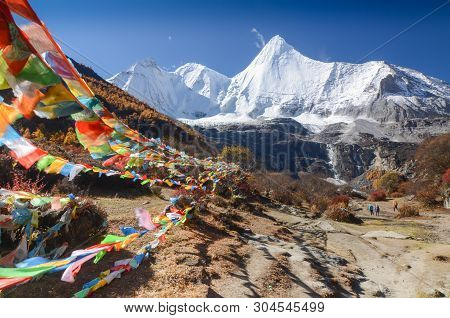Colorful Tibetan Flags And Snow Mountain At Yading Nature Reserve In Autumn Season, The Last Shangri