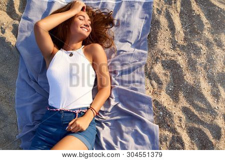 Young Tanned Pretty Woman Laying In The Sun On Beach Towel. Attractive Stylish Fashionable Female Li
