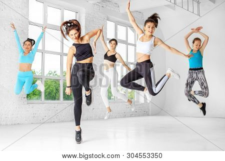 A Group Of Girls Jumping To Dance In The Dance Class. The Concept Of Sports, A Healthy Lifestyle, Fi