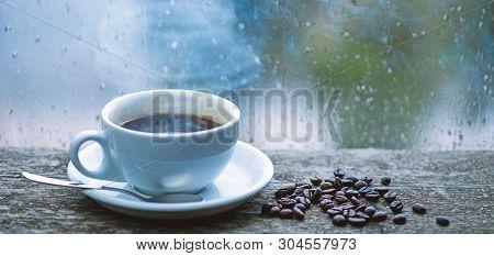 Enjoying Coffee On Rainy Day. Coffee Morning Ritual. Fresh Brewed Coffee White Mug And Beans On Wind