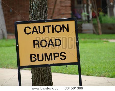 A City Street Runs Through The Campus Of A Large Colonial-style Church. The Sign Warns Of Road Bumps
