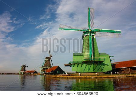 Ancient Green Windmill Located In Zaanse Schans, A Small Dutch Community Along The Quay Of The River