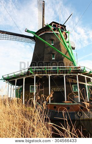 Old Dutch Wooden Windmill In Zaanse Schans On The Water Of The River Zaan