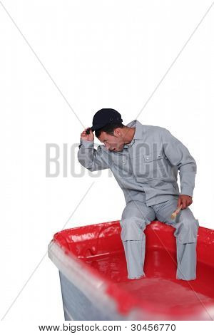 Surprised man sitting on a paint can