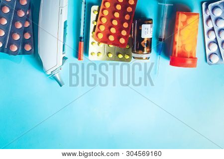 Healthcare Concept - Pills And Medical Thermometr Boder On Blue Background, Toned