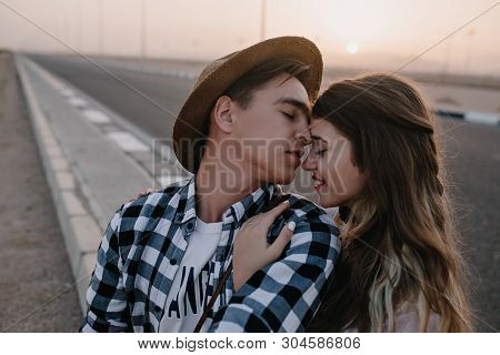 Long-haired Attractive Girl Gently Embracing Her Boyfriend In Stylish Shirt With Eyes Closed On Blur