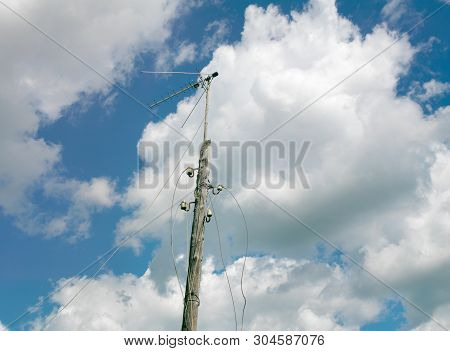Abandoned Wooden Electrical Post With Dandling Wires Against The Blue Sky, Concept Of A Blackout