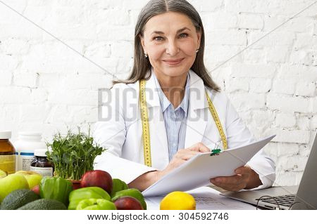 Horizontal Shot Of Beautiful Positive Elderly Female Nutritionist Having Consultation With Client At