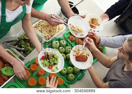 Volunteers Serving Food For Poor People Indoors, View From Above