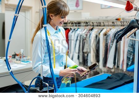 Employee in dry-cleaning company working with tools in hand