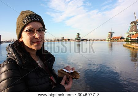 Caucasian Tourist Girl Dressed In Winter Clothes Walks Among The Canals Of The Zaan River, In Zaansc
