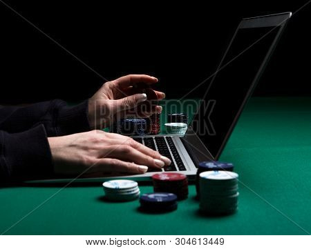 Woman Playing Online Poker With Laptop On A Green Table With Chips All Around, Side View