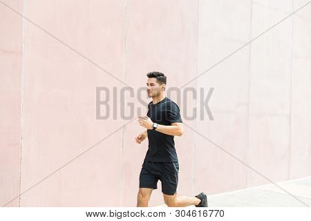 Dedicated male jogger running by wall in city poster