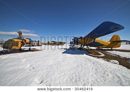 Old Airplanes Parked On A Meadow With Snow