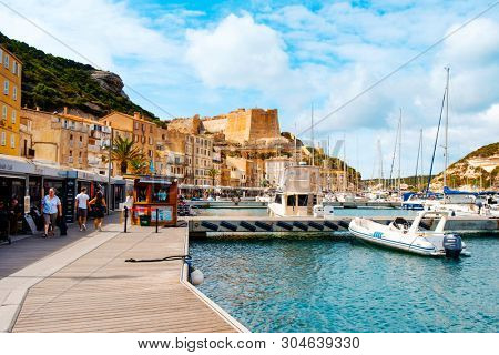 BONIFACIO, FRANCE - SEPTEMBER 19, 2018: People walking by the port of Bonifacio, in Corsica, France, with the famous citadel of the city in the background, on the top of a promontory