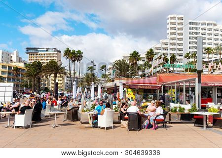 MASPALOMAS, SPAIN - JANUARY 21, 2019: Vacationers at the restaurant terraces of Playa del Ingles, in Maspalomas, in the Canary Islands, Spain, a popular winter beach destination for European people
