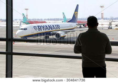 Boryspil, Ukraine - March 23, 2018: Man Watch Through The Window To The First Ryanair Plane Landed A