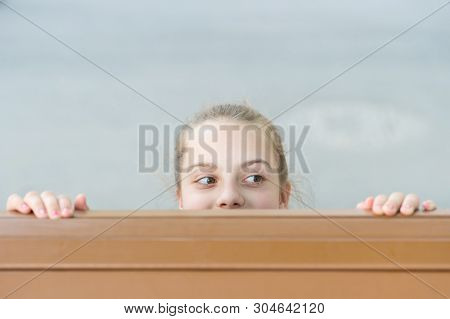Secret Place For Hiding. Cute Small Child Hiding Under The Table. Little Girl Hiding And Peeping Out