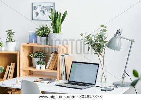 Table lamp, laptop, copybooks and books on desk and shelves with green domestic plants in flowerpots inside office