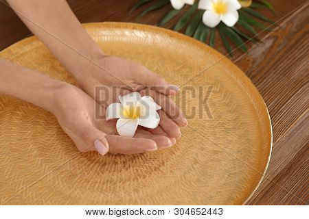 Woman soaking her hands in bowl with water and flowers on table, closeup. Spa treatment poster