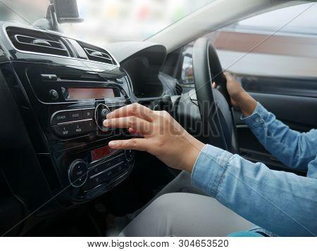 Female Driver's Hand Press Button On Car Radio