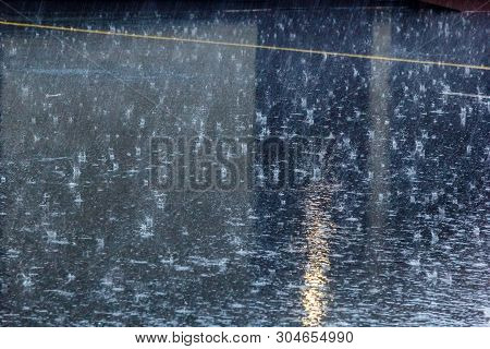 The Pouring Rain, With A Thunderstorm And A Thunder, Water Flows On Asphalt Forming Pools, Drops Of