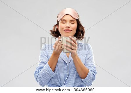 people and bedtime concept - happy young woman in pajama and eye sleeping mask drinking coffee from mug over grey background