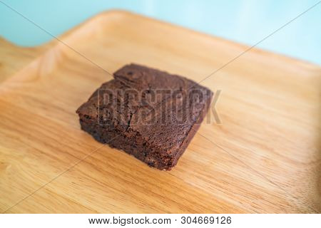 Chocolate brownies on wooden surface.